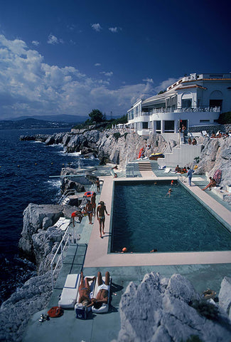 A photograph captured in 1976 of the amazing cliff-side pool at the Hotel du Cap in Antibes, France, with guests relaxing poolside.