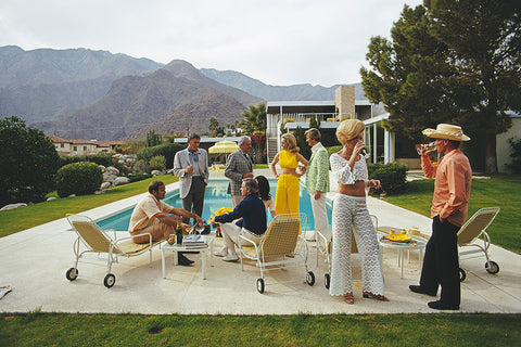 A photograph of a Mid Century Modern home in Palm Springs, captured in 1970 by Slim Aarons featuring partygoers by the pool.
