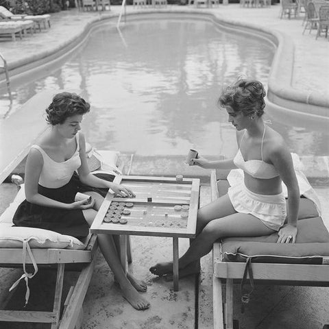 A vintgae black and white photography of two ladies in swimming costumes playing backgammon by the swimming pool, circa 1959.