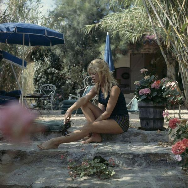 A candid photograph of Brigitte Bardot sitting on a step in a garden, looking down. She wears a tank top, shorts, a hair bow and is loosely holding a pair of black sunglasses.