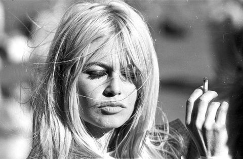 A vintage black and white photograph, a close up of Bridget Bardot smoking a cigarette.