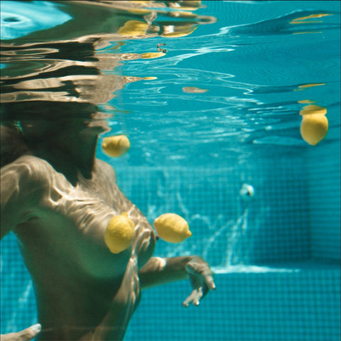 A serene photograph of a woman wading in the water nude. The photograph is from the waist up and bright yellow lemons surround her in the pool carefully positioned to cover her.
