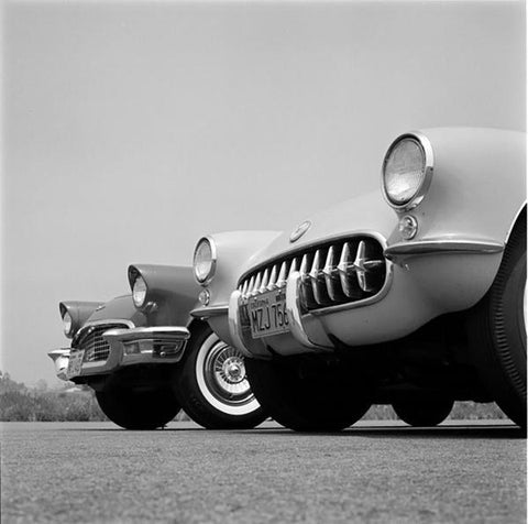 A black and white close up photograph of two vintage cars.