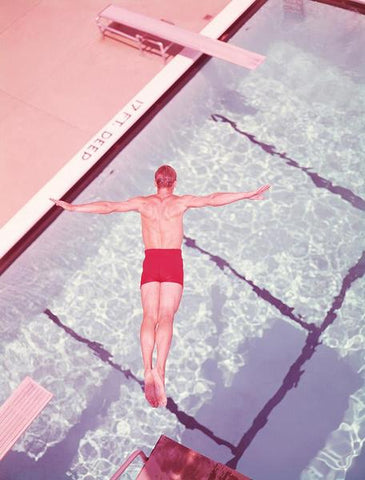 A vintage photograph of a man diving off a diving board into a pool in pastel tones.