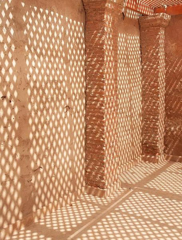 An abstract photograph of a dappled light on a traditional Morroccan building in rust tones.