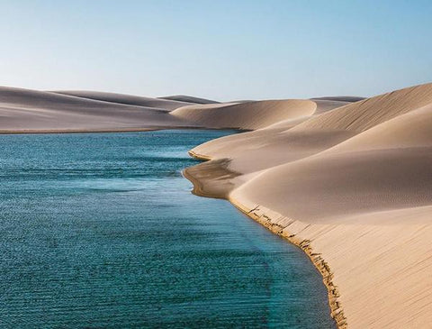 A photograph of the water's edge and sand dune landscape of Lencois Maranhenses, Brazil.