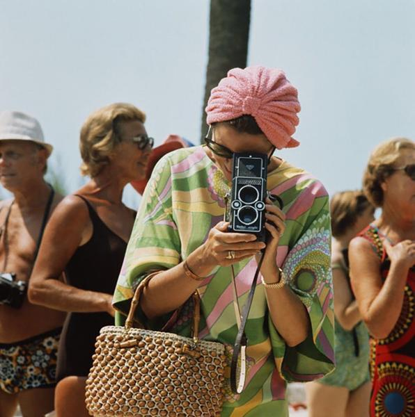Princess Grace of Monaco taking a photograph. She wears a pink and green 70s style dress and pink hair wrap.