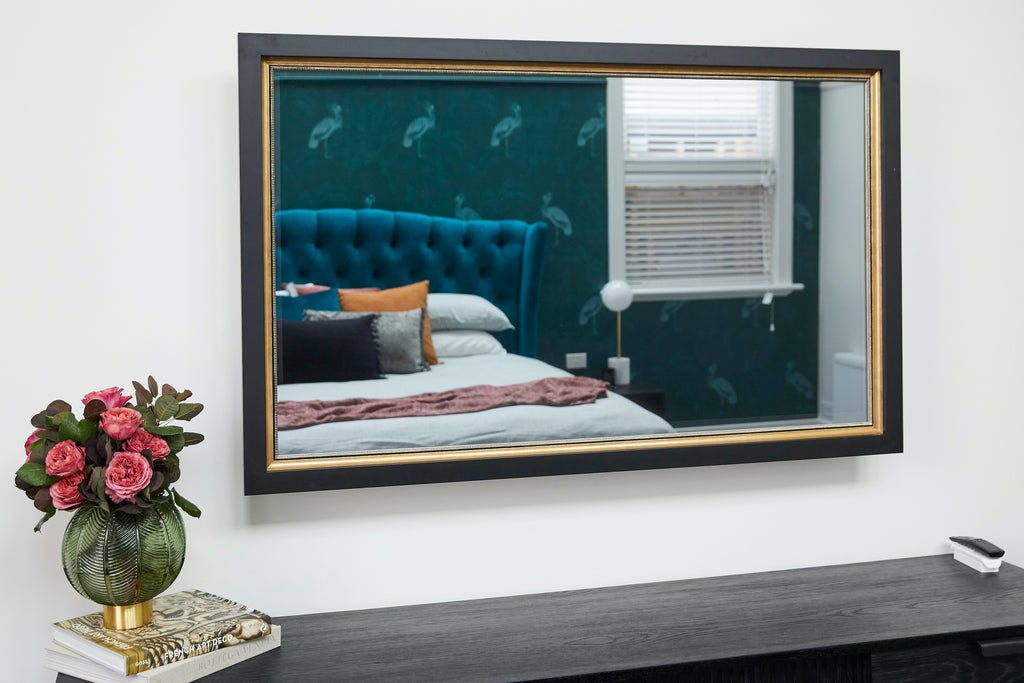 A TV Mirror with a black and gold frame with a bed in the reflection