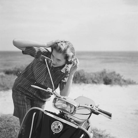 A vintage black and white photograph of a young lady checking her hair in the mirror of a motor scooter, Bermuda, 1958.