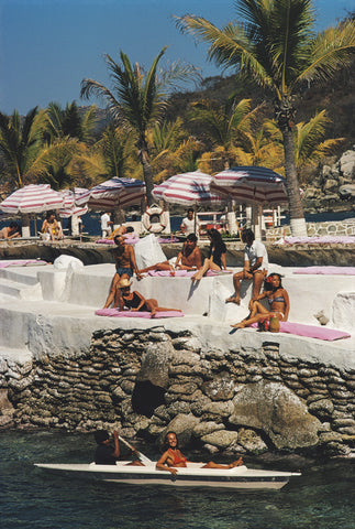 A photograph captured in 1972 of holidaymakers relaxing on pink sun-lounges, with striped pink umbrellas on the cliff-side of a beach resort. The water below is a deep blue and a lady relaxes in a boat in the ocean below.