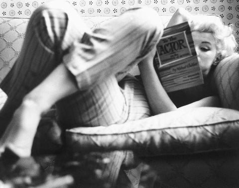 Marilyn Monroe candidly reads a book laying on the couch with her legs crossed.