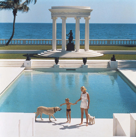 Standing in fron of her Grecian pool, C.Z Guest holds her son's hand while their two dogs stand beside them.
