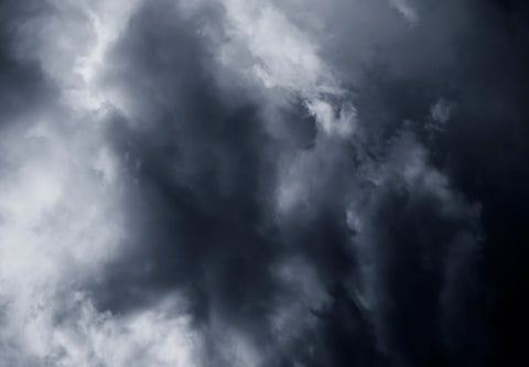 A photograph of clouds in dark grey tones.