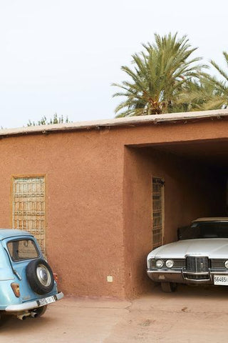 A photograph of two vintage cars parked outside a terracotta building.