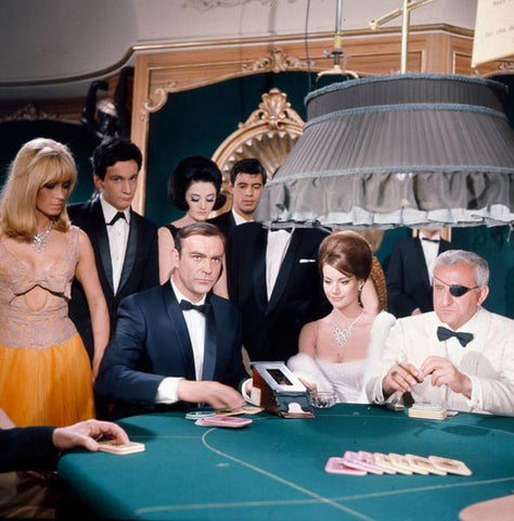 Seated around a poker table, Scottish actor Sean Connery, as James Bond wiith Italian actor Adolfo Celi as eye patch wearing Emilio Largo are captured in the iconic casino scene from the film 'Thunderball' in 1965. Glamorous onlookers are dressed in exquisite gowns and tuxedos.
