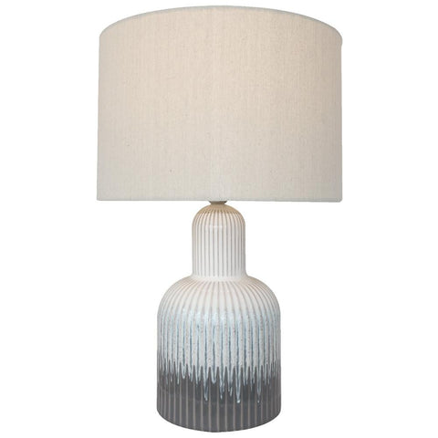 A ceramic base lamp in neutral tones with a soft natural shade.