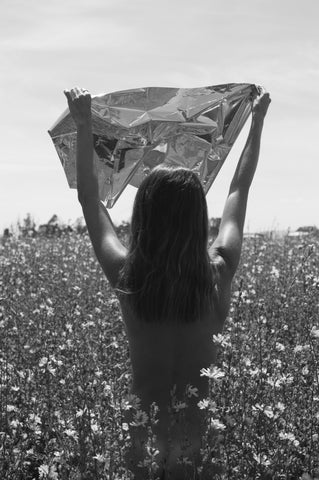 A black and white photograph of a girl in a field of flowers. The photograph is taken from behind the girl and she raises her arms up holding some silver cellophane.