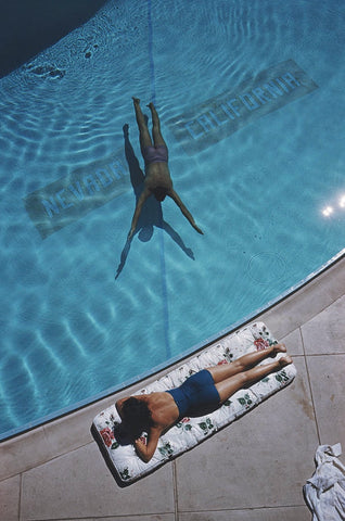 A man swims under the water towards the edge of a pool while a woman lays in the sun by the water's edge on a floral sunlounge.