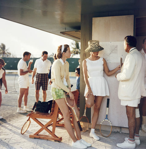 A photograph captured in 1957 of holidaymakers standing by a tennis court chatting.