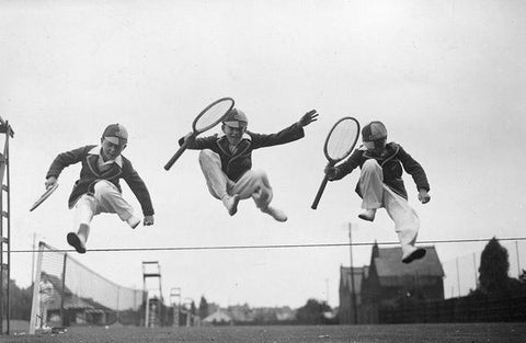 A playful vintage photograph of three young competitors leaping over the boundary between two tennis courts, wearing 1930s schoolboy uniforms.