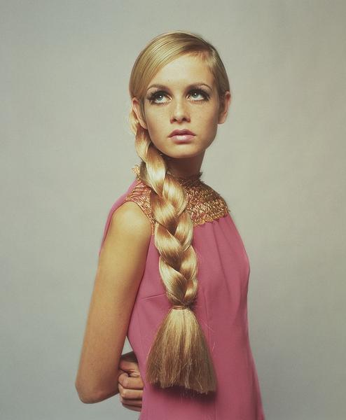 A vintage photograph of model Twiggy wearing a pink shift dress with a long, large plait.