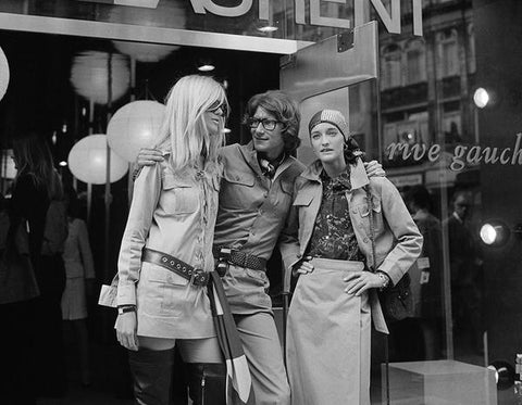 A black and white vintage photograph of Yves Saint Laurent, French designer posing with two fashion models, Betty Catroux (left) and Loulou de la Falaise, outside his 'Rive Gauche' shop.