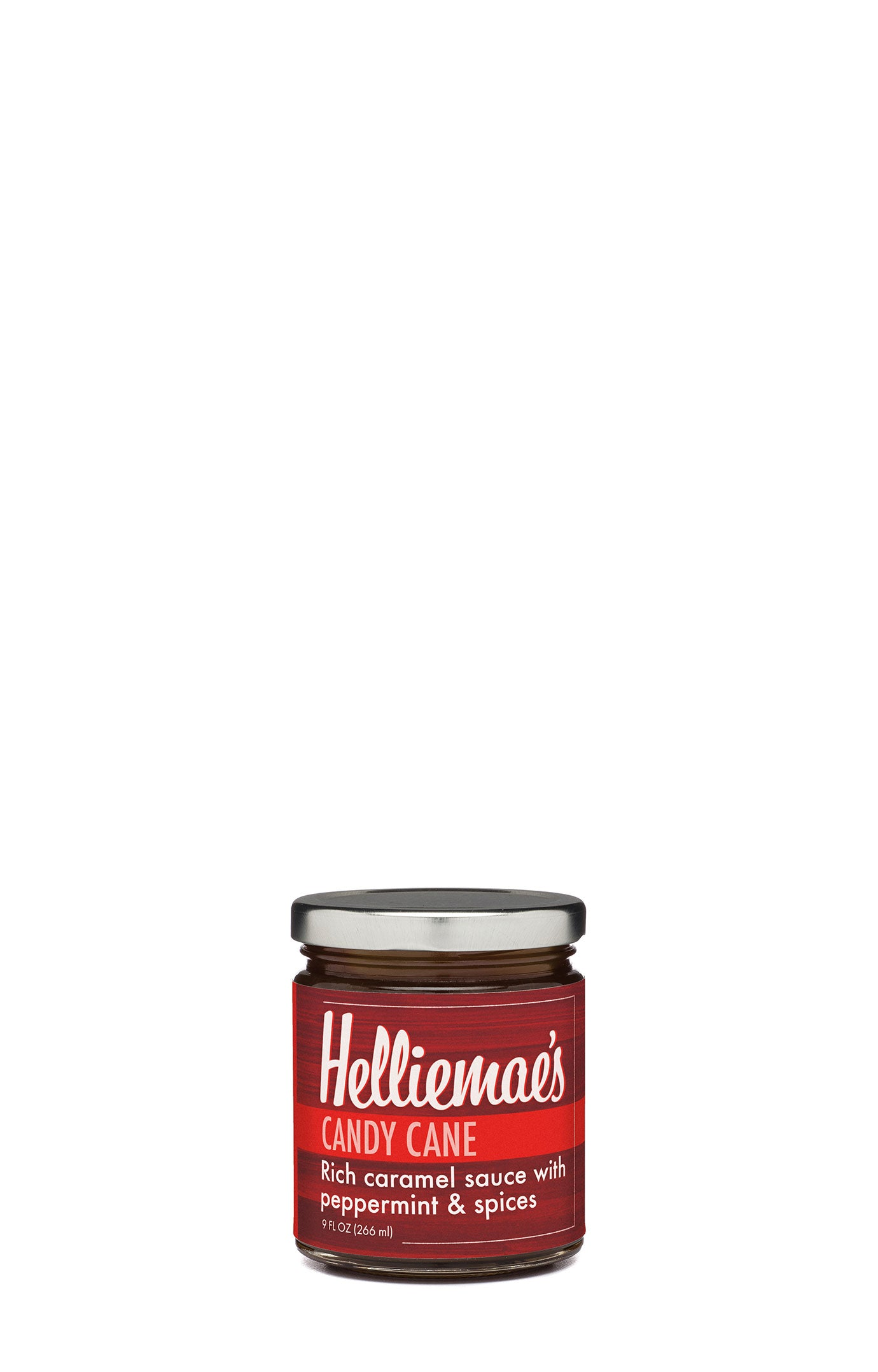 Helliemae's Candy Cane Caramel sauce, clear straight-sided jar with silver lid and colorful red label, with effect of milk paint on a barn wall.