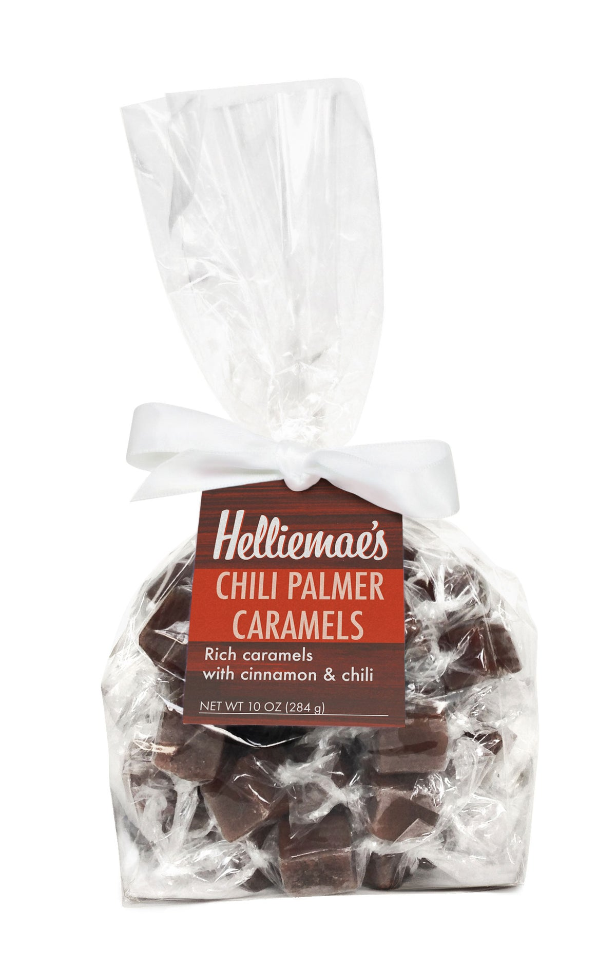 Helliemae's Chili Palmer Caramels large gift bag, clear cello bag with gathered top, fastened with white satin ribbon and colorful orange hangtag, with effect of milk paint on a barn wall.