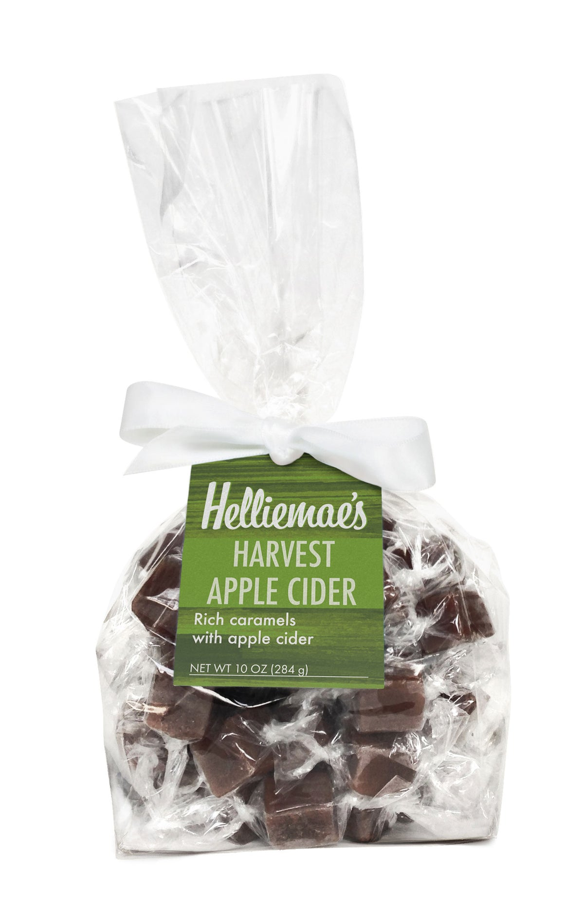 Helliemae's Harvest Apple Cider Caramels large gift bag, clear cello bag with gathered top, fastened with white satin ribbon and colorful green hangtag, with effect of milk paint on a barn wall.