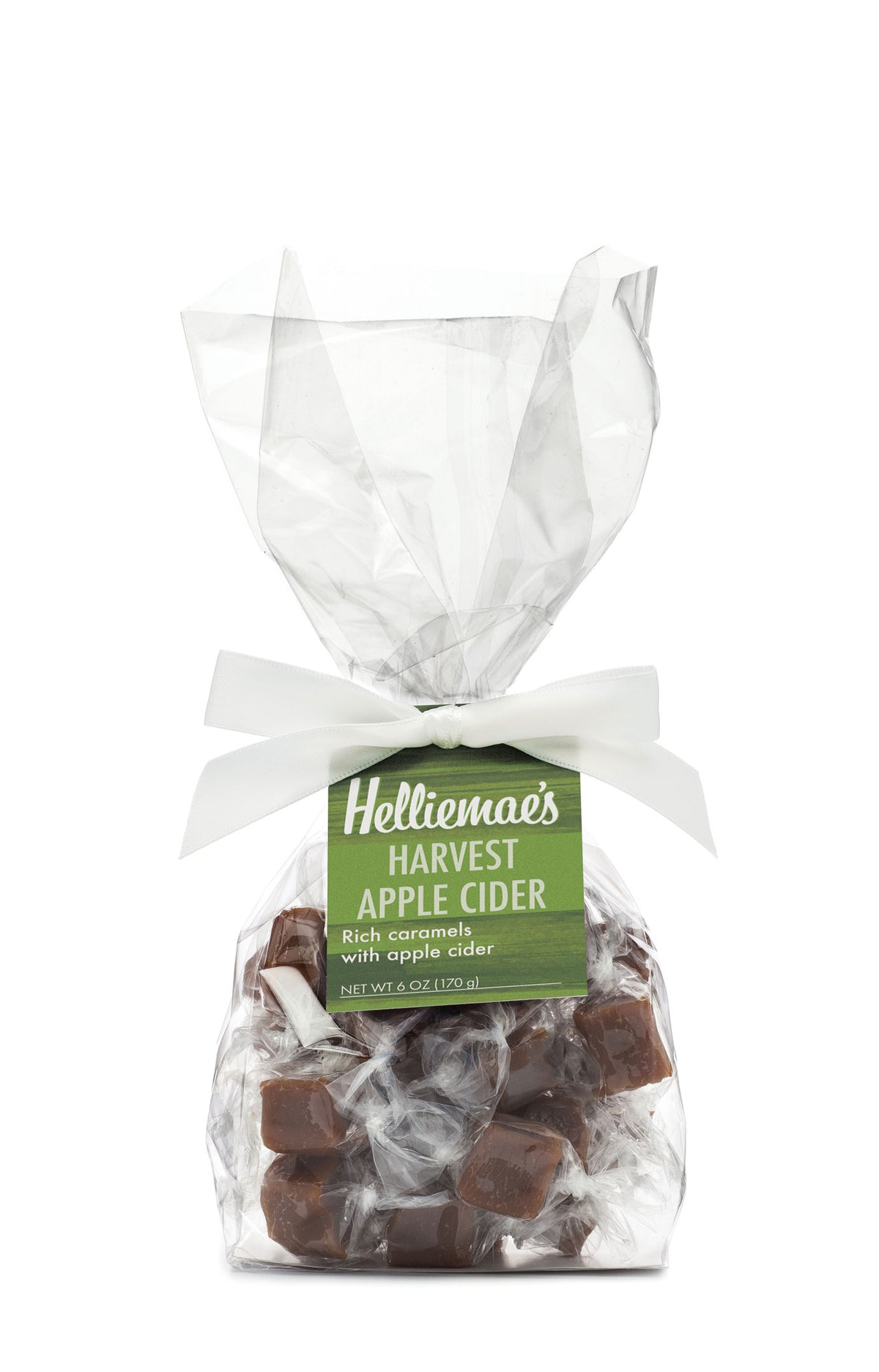 Helliemae's Harvest Apple Cider Caramels medium gift bag, clear cello bag with gathered top, fastened with white satin ribbon and colorful green hangtag, with effect of milk paint on a barn wall.