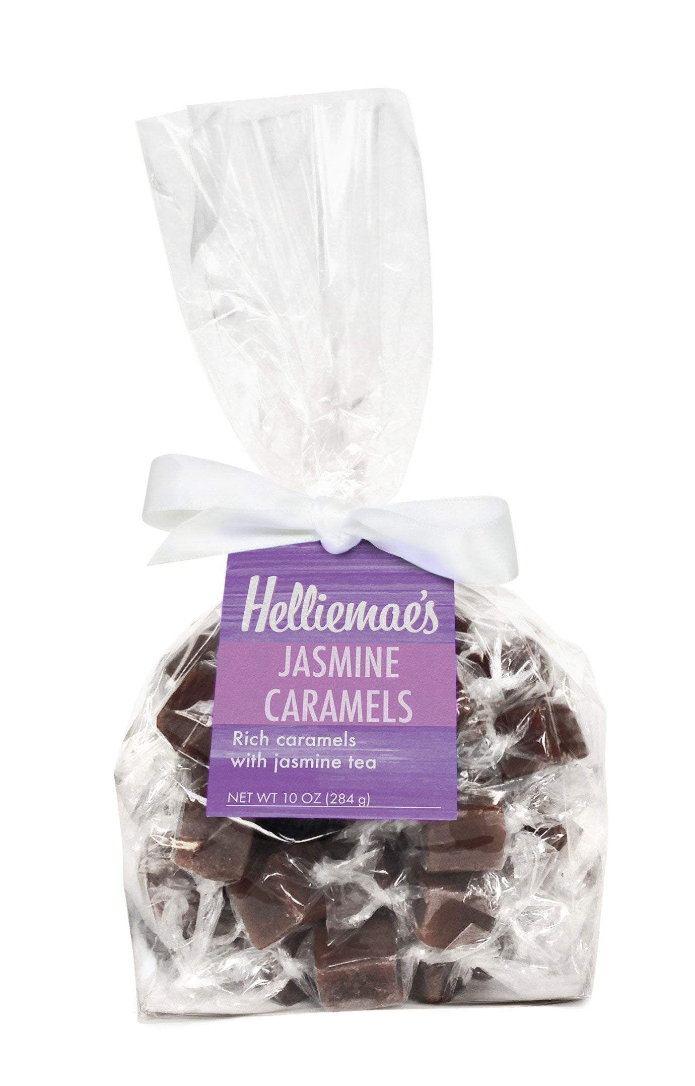 Helliemae's Jasmine Caramels large gift bag, clear cello bag with gathered top, fastened with white satin ribbon and colorful lavender hangtag, with effect of milk paint on a barn wall.