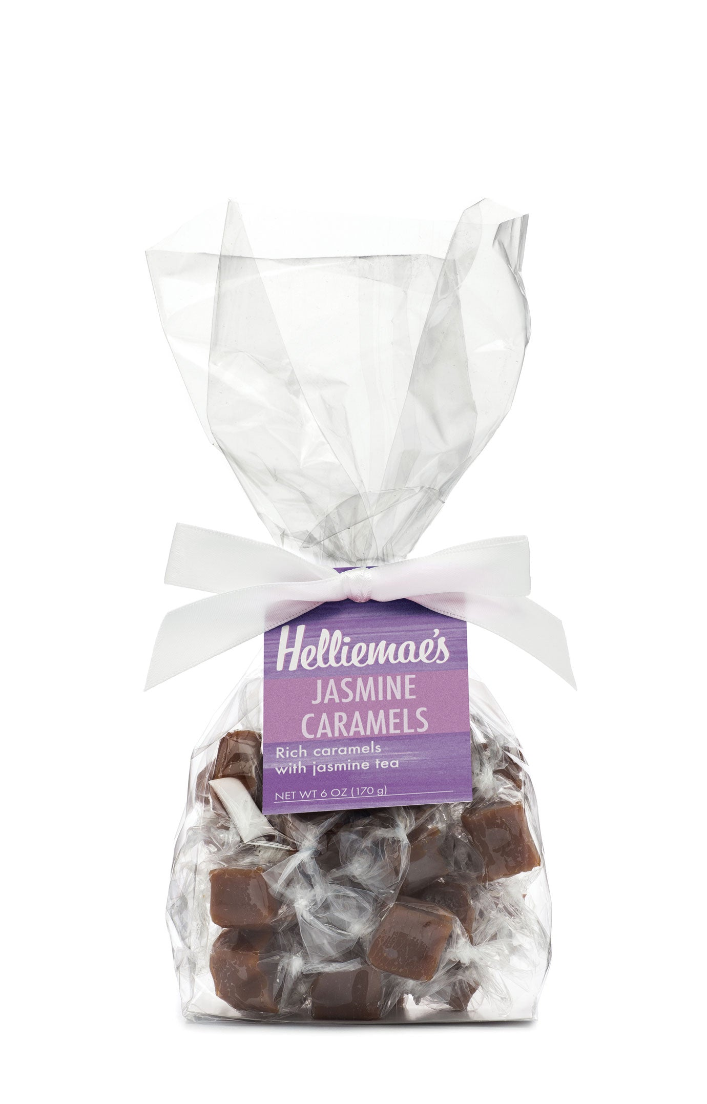Helliemae's Jasmine Caramels medium gift bag, clear cello bag with gathered top, fastened with white satin ribbon and colorful lavender hangtag, with effect of milk paint on a barn wall.