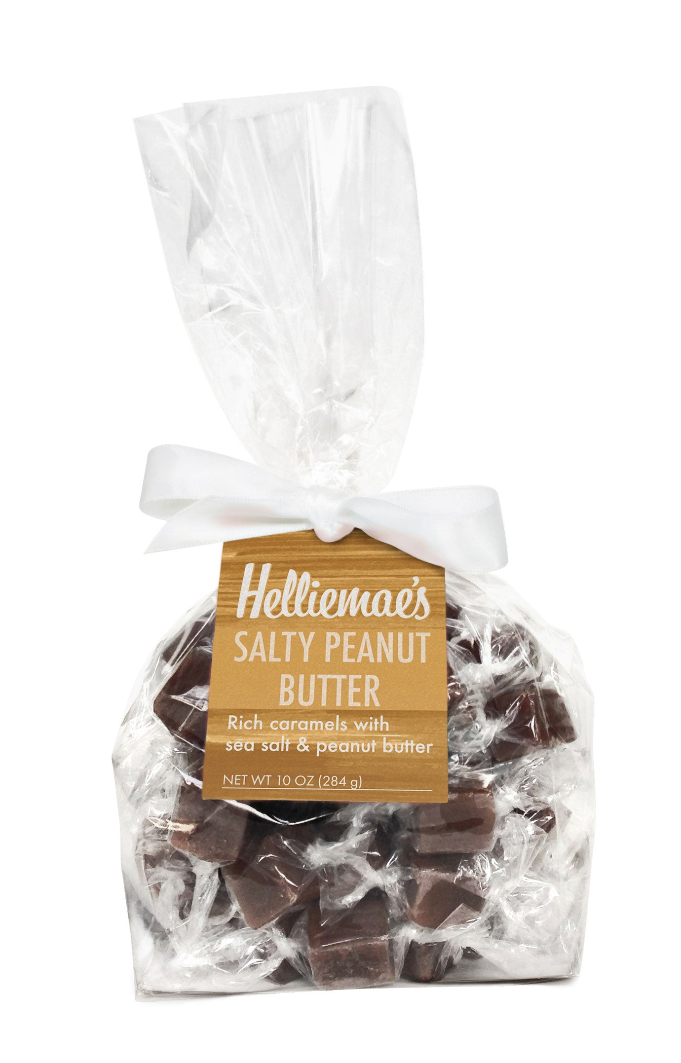 Helliemae's Salty Peanut Butter Caramels large gift bag, clear cello bag with gathered top, fastened with white satin ribbon and colorful tan hangtag, with effect of milk paint on a barn wall.