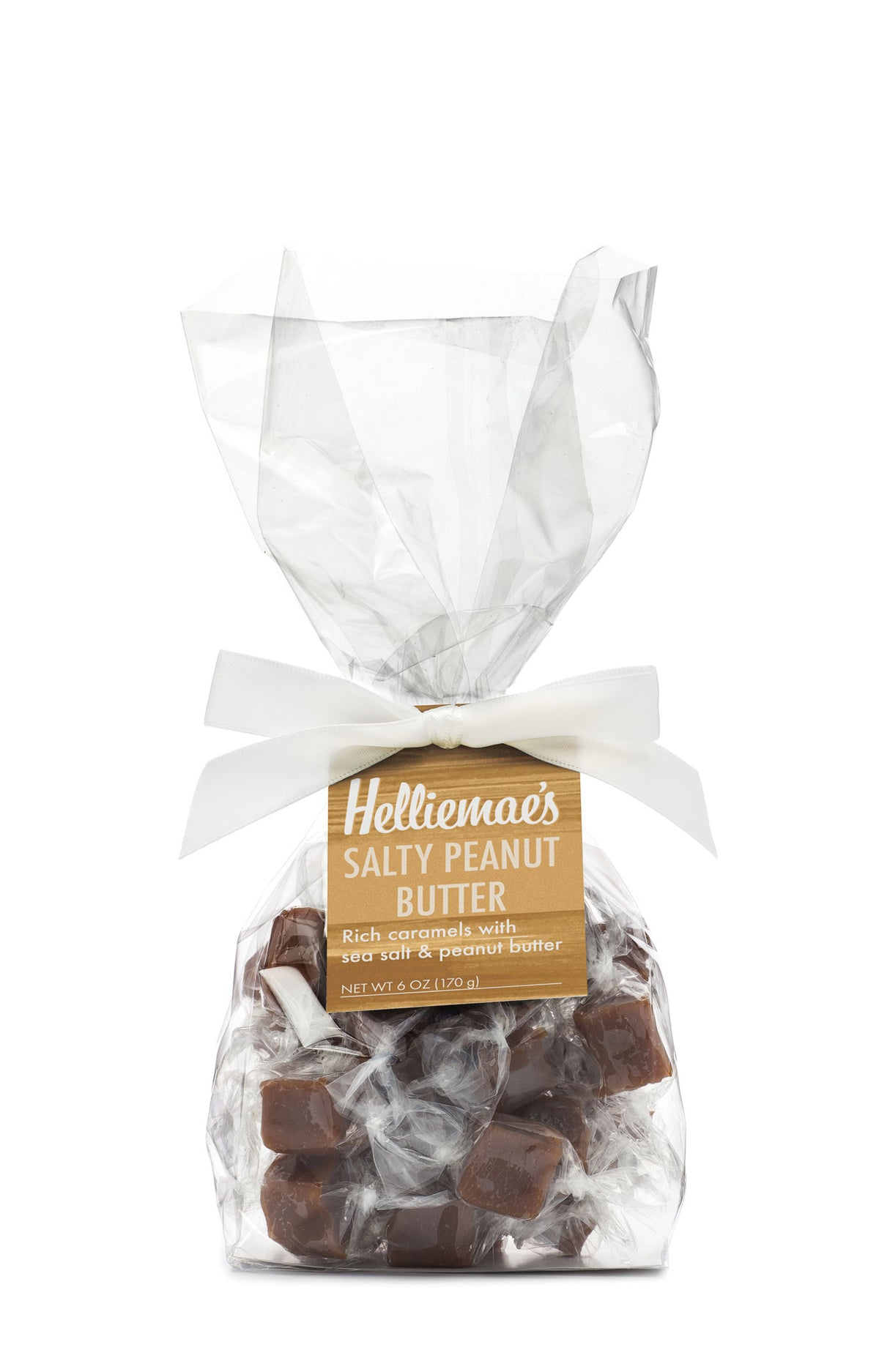 Helliemae's Salty Peanut Butter Caramels medium gift bag, clear cello bag with gathered top, fastened with white satin ribbon and colorful tan hangtag, with effect of milk paint on a barn wall.