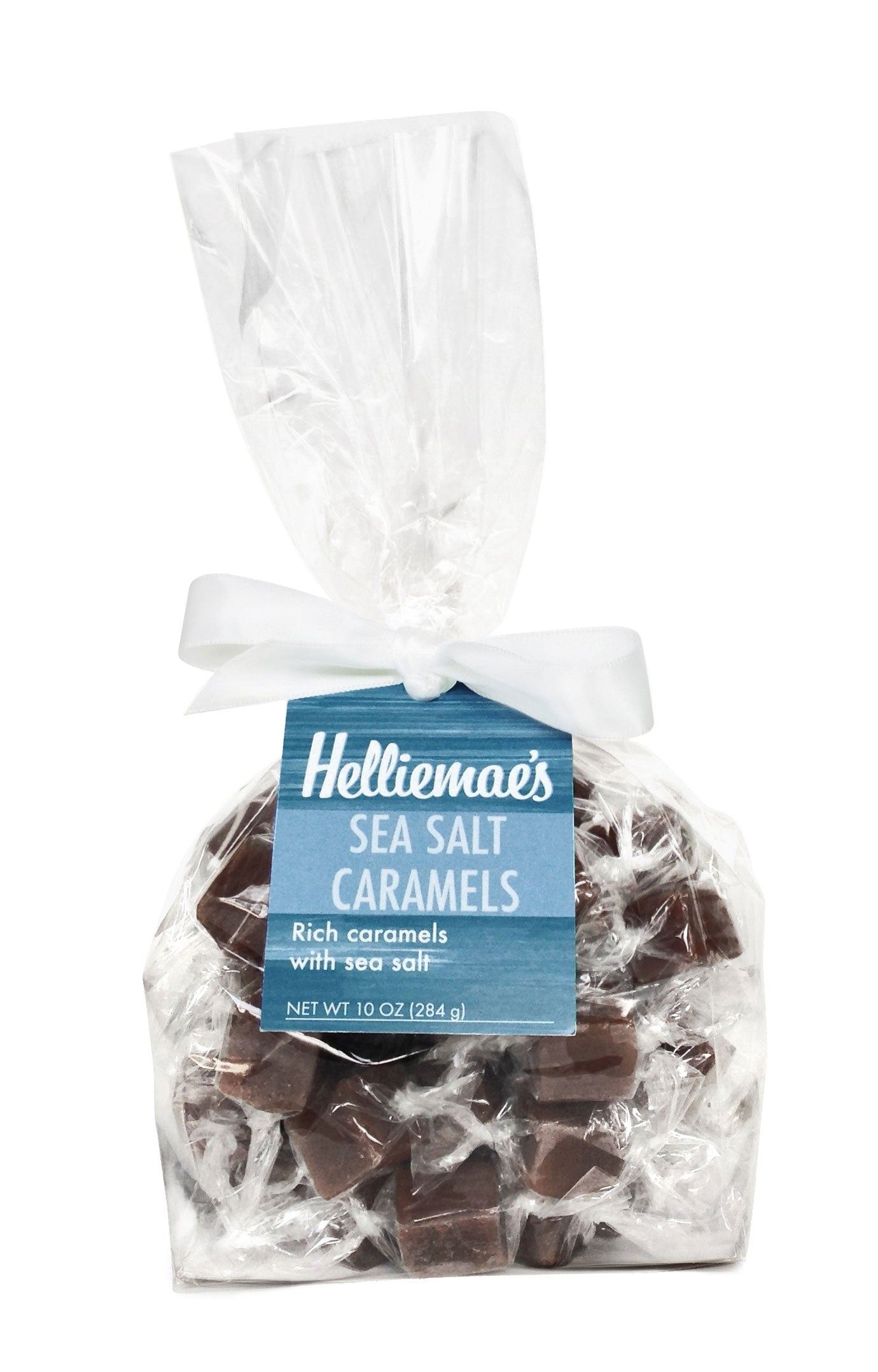 Helliemae's Sea Salt Caramels large gift bag, clear cello bag with gathered top, fastened with white satin ribbon and colorful blue hangtag, with effect of milk paint on a barn wall.