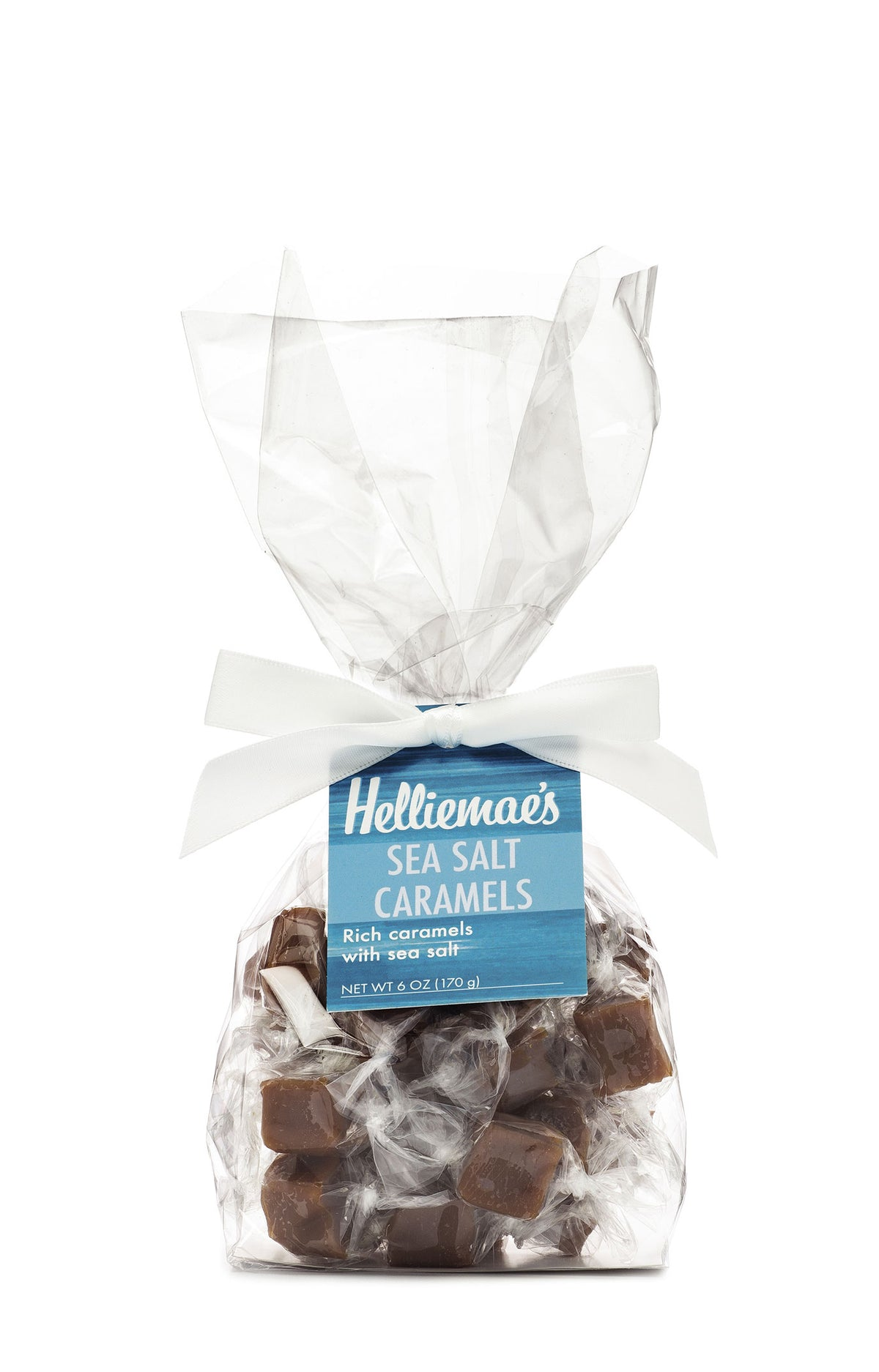 Helliemae's Sea Salt Caramels medium gift bag, clear cello bag with gathered top, fastened with white satin ribbon and colorful blue hangtag, with effect of milk paint on a barn wall.