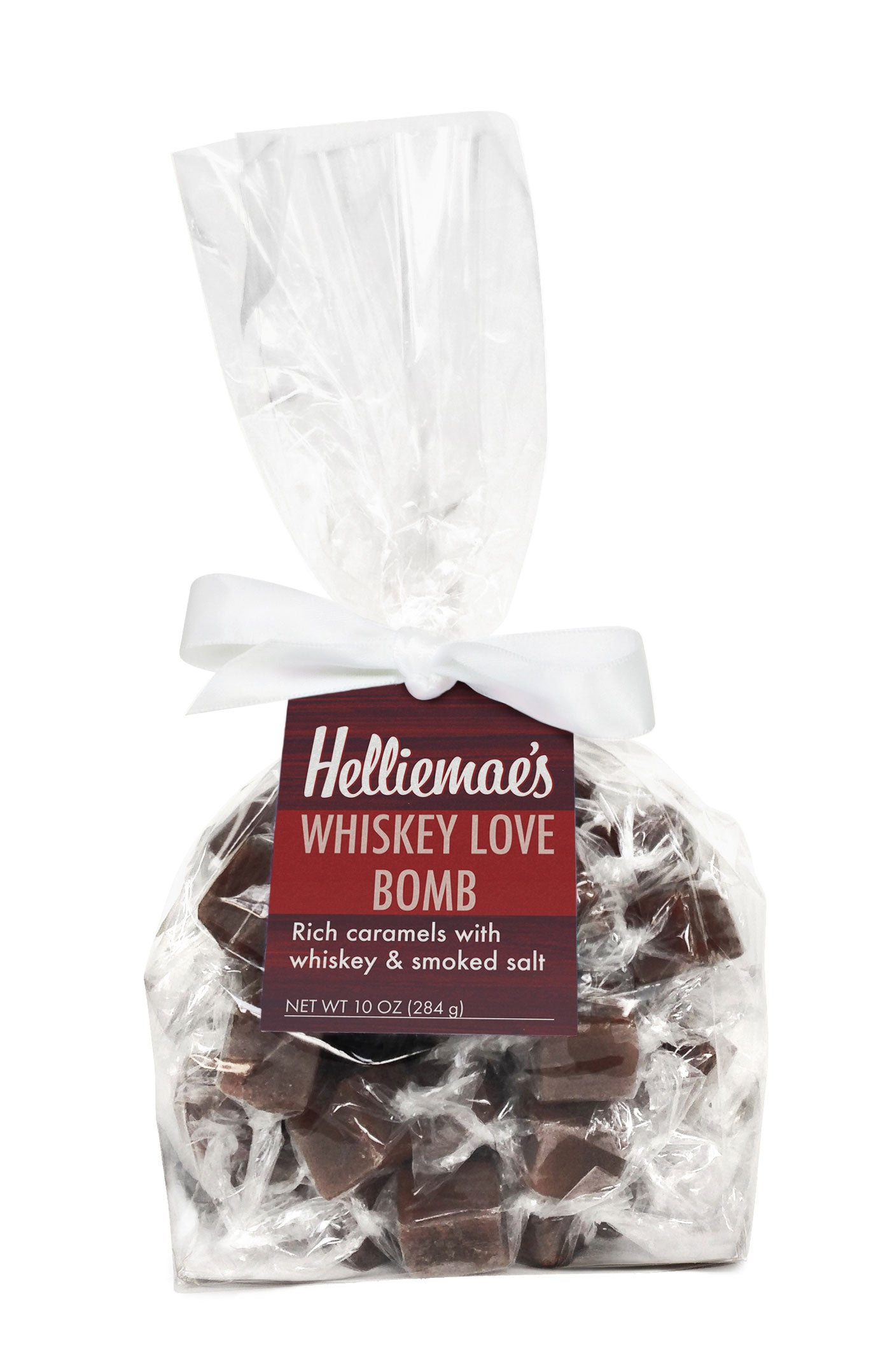 Helliemae's Whiskey Love Bomb Caramels large gift bag, clear cello bag with gathered top, fastened with white satin ribbon and colorful maroon hangtag, with effect of milk paint on a barn wall.