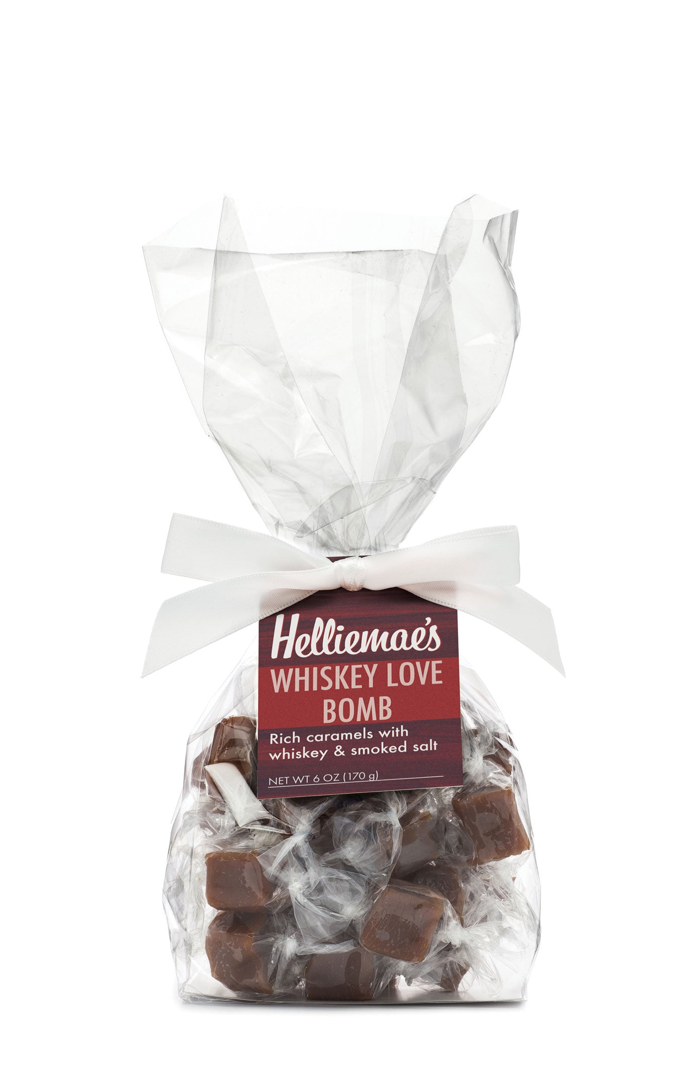 Helliemae's Whiskey Love Bomb Caramels medium gift bag, clear cello bag with gathered top, fastened with white satin ribbon and colorful maroon hangtag, with effect of milk paint on a barn wall.