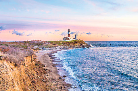 Ocean view of Montauk Point Lighthouse in Montauk, New York at sunset with a small cliff on the left overlooking the water on the right