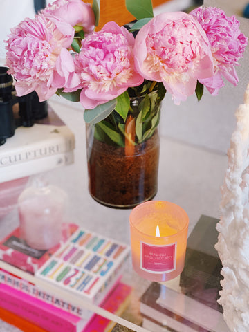 Iridescent pink candle in a holographic vessel next to peonies by Malibu Apothecary
