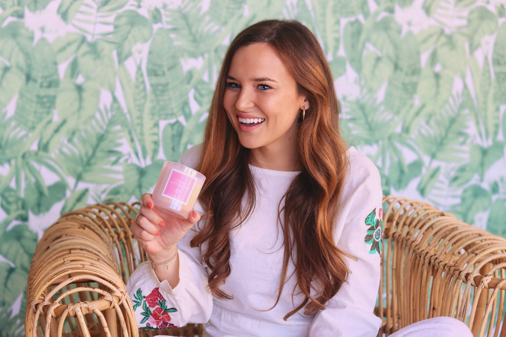 Malibu Apothecary Founder Claire Ellis sitting on a chair holding our holographic iridescent pink candle
