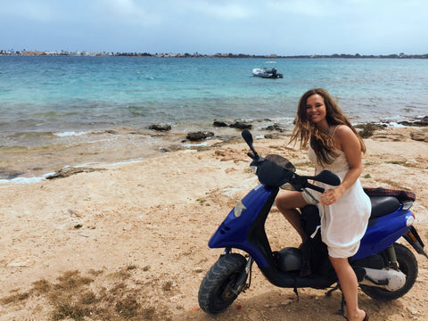 Malibu Apothecary Founder Claire Ellis on a beach in Formentera, Spain near Ibiza on a motorcycle
