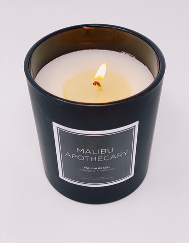 Candle burning in matte black from Malibu Apothecary with a white background