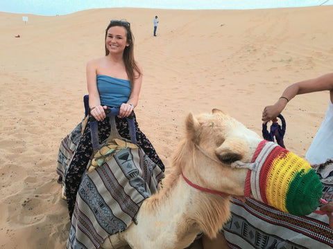 Malibu Apothecary Founder Claire Ellis on a Camel in the desert in Dubai