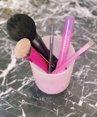 Reusing candle container in hot pink with makeup brushes on black marble bathroom counter by Malibu Apothecary