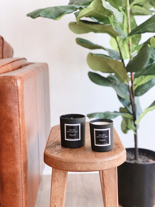 Malibu Apothecary matte black candle and mini black matte candle on a wood table in a living room with a fiddle leaf fig tree in the background