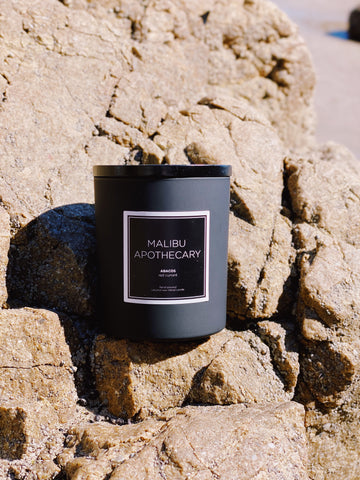 Matte black candle by Malibu apothecary on a rock at the beach in Malibu