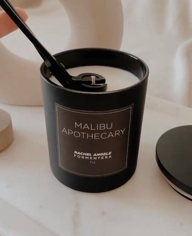 trimming a wick on a matte black custom candle by Malibu Apothecary