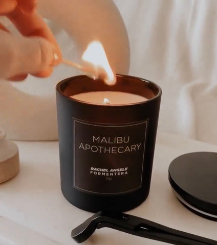 Custom Candle in Matte Black Being Burned with a Match by Malibu Apothecary