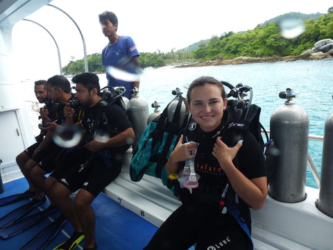 Malibu Apothecary Founder, Claire Ellis, on a diving boat with diving gear in Phuket, Thailand